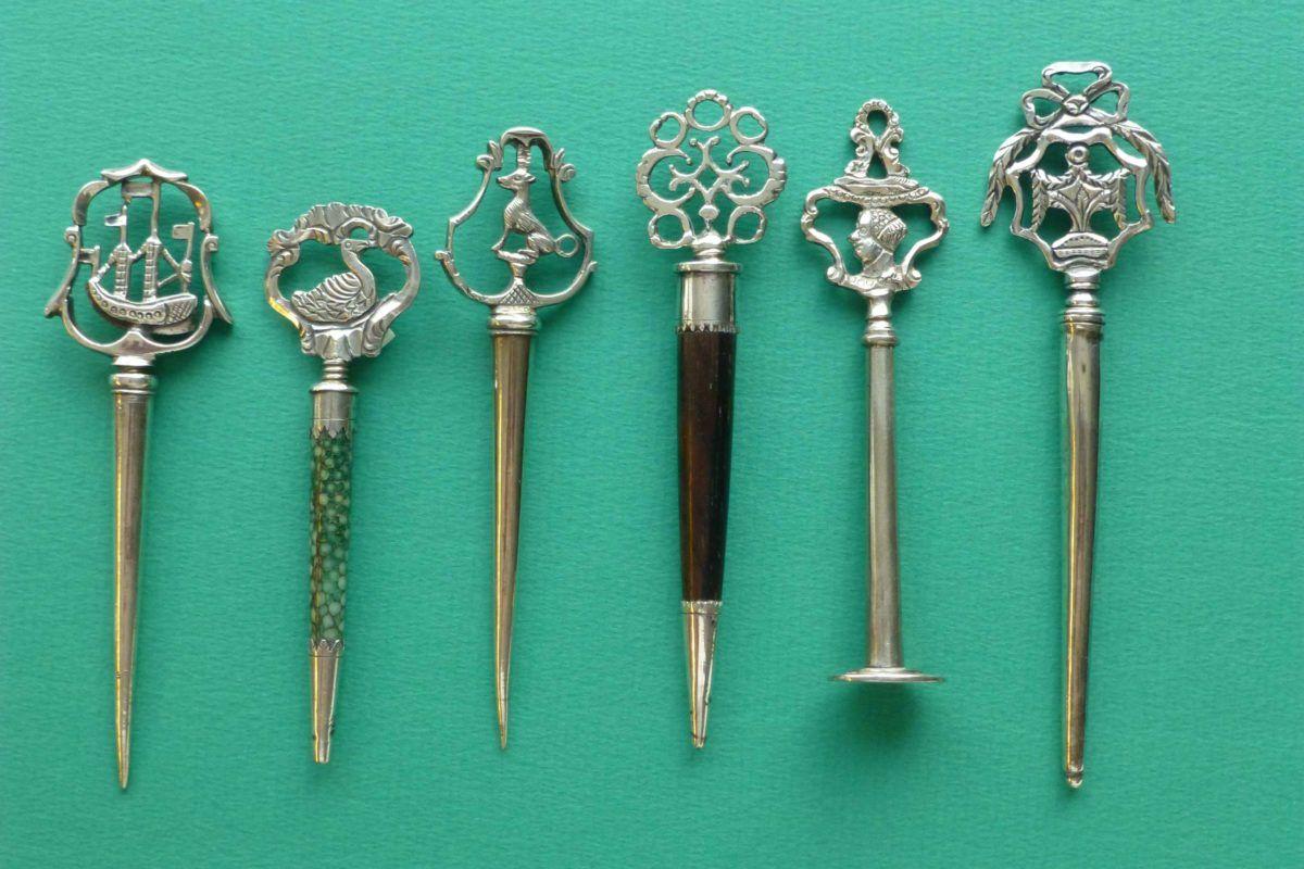 antieke zilveren priemen met verschillende bekroningen en schedes.