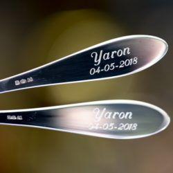 Kinderbestek gegraveerd met een naam en datum gecentreerd onder elkaar
